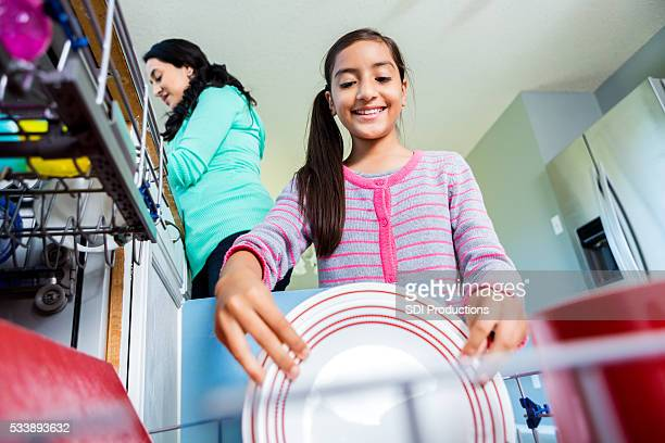 Happy pre-teen girl helps mom in the kitchen