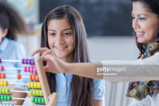 Happy preteen girl uses abacus at school