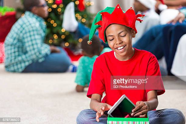 Happy pre-teen in elf hat gets tablet for Christmas