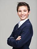Happy pretty teenage boy posing at studio as a fashion model.