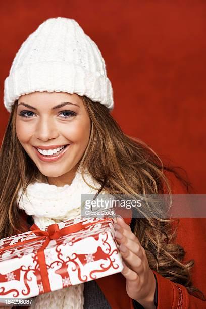 Heureuse jolie femme tenant un cadeau de Noël