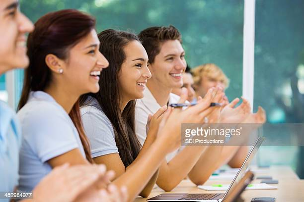 Happy private school students applauding during lecture
