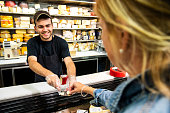 A happy young employee in the cheese section of a specialty grocery store offering a customer a sample of cheese.