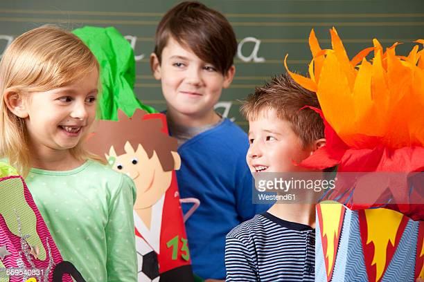 Happy pupils with school cones at blackboard