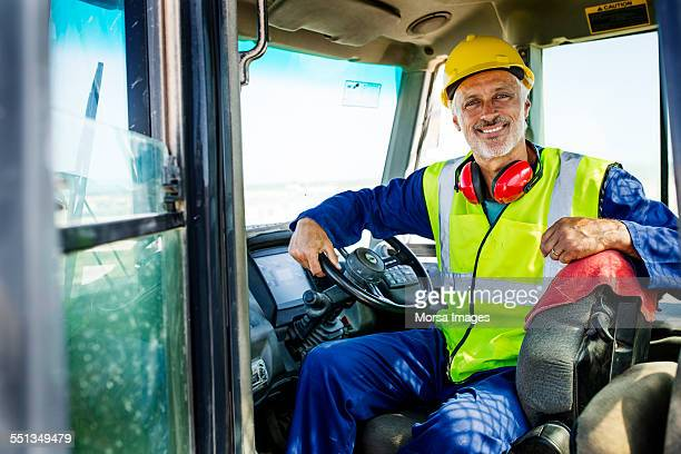 Happy quarry worker sitting in bulldozer