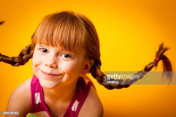 Happy, Red-Haired Girl with Upward Braids and a Smile