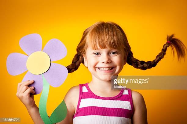 Glücklich Rotes männlichen Mädchen mit nach oben, geflochtener Zopf Holding Papier mit Blume