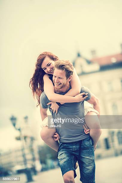 Happy redhead couple piggybacking.