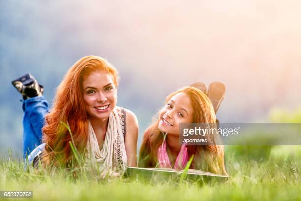 Happy redhead sisters reading book outdoors in park.