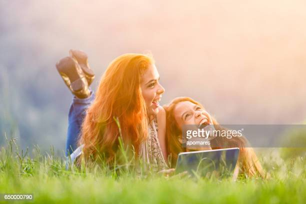 Happy redhead sisters using tablet outdoors in park.
