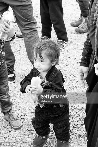 Happy refugee toddler eating sandwich provided by volunteer