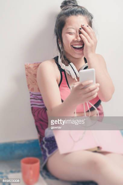 Happy relaxed Asian female student using mobile phone.