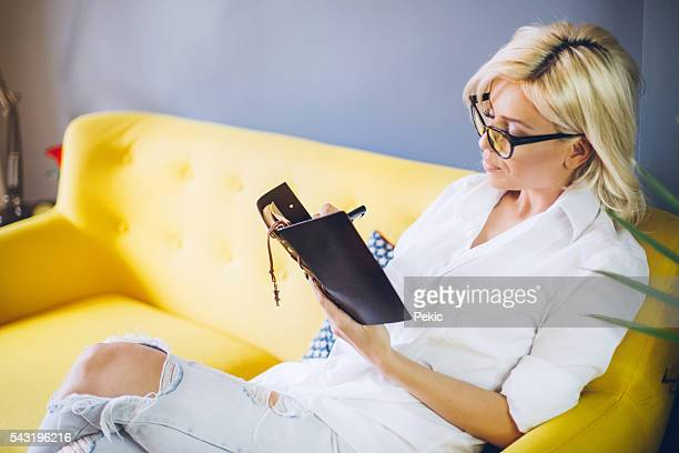 Happy relaxed blonde woman writing in her diary