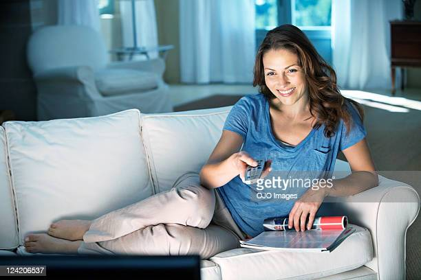 Happy relaxed mid adult woman holding remote control at home