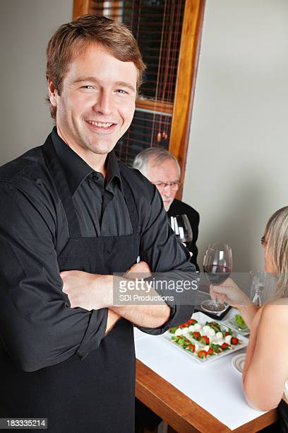 Happy Restaurant Waiter In Front of His Table