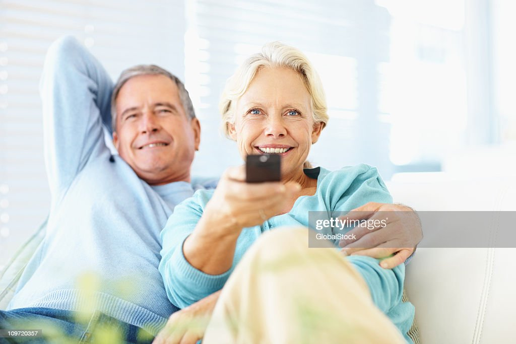 Happy retired couple watching TV at home : Stock Photo