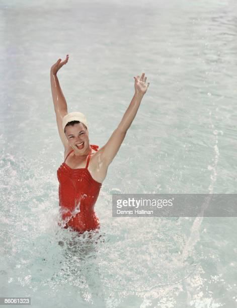 Happy retro girl splashing water with arms raised