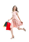 Happy running beautiful woman with many colorful shopping bags isolated on white background. Full length portrait