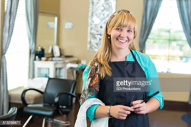 Happy salon hairstylist holding scissors and comb