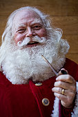 A happy Santa Claus laughing, holding his pipe