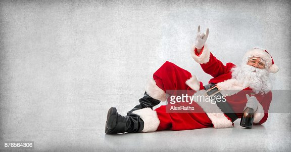 Happy Santa Claus lying on the floor with a bottle of wine : Foto de stock