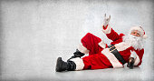 Drunk and happy Santa Claus lying on the floor with a bottle of wine and makes a hand sign