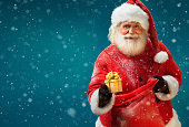 Happy Santa Claus with gift on blue background. Merry Christmas & New Year's Eve concept.