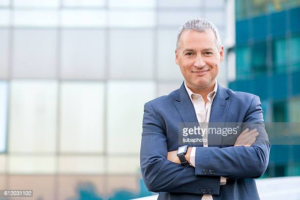 Happy satisfied mature businessman looking at camera