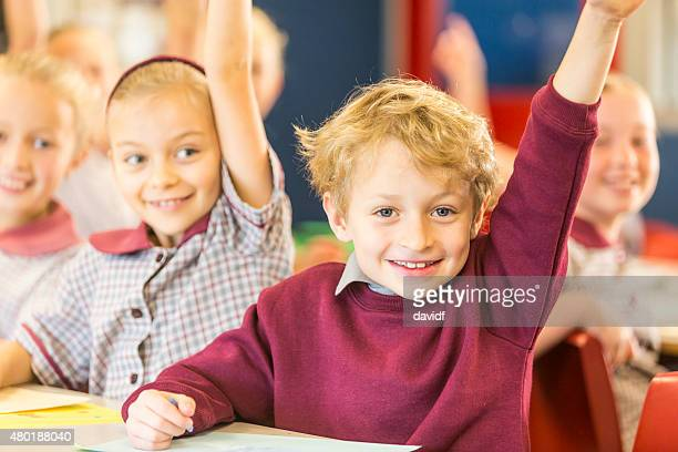 Happy School Boy Answering a Question in the Classroom