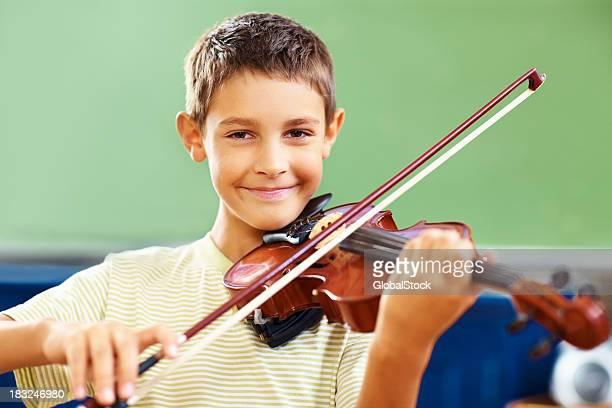 Happy school boy practicing the violin