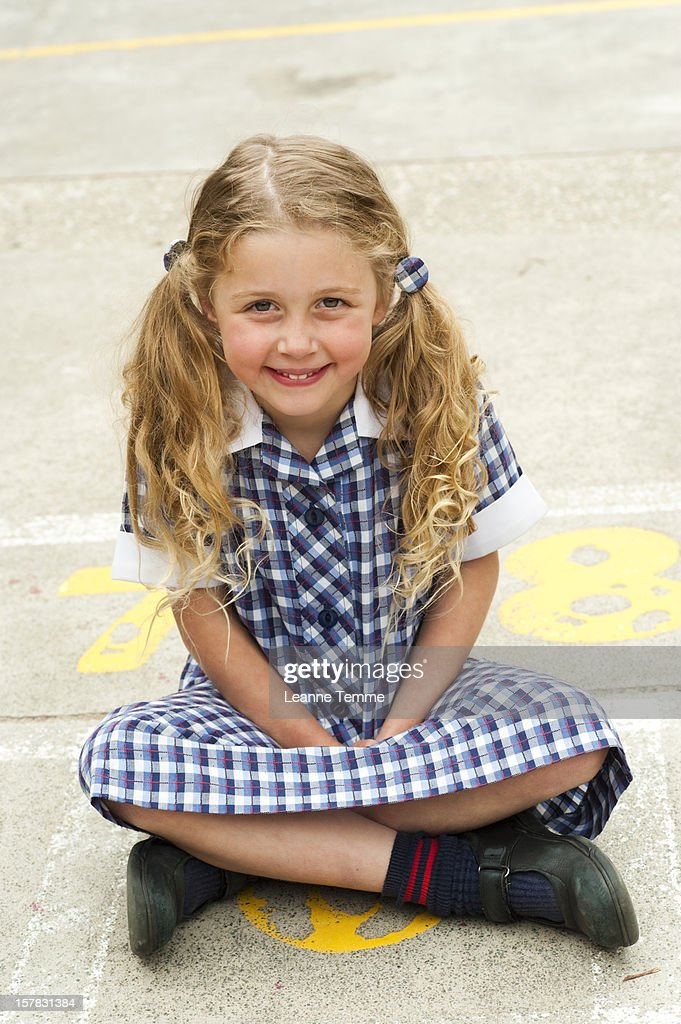 Happy school girl sitting down outside : Stock Photo