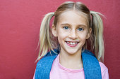 Portrait of beautiful schoolgirl wearing backpack and looking at camera. Closeup face of cute little girl with pigtails smiling isolated on red background. Blonde young girl with two pony tail before