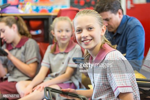 Happy School Girl Using Tablet Computer In The Classroom
