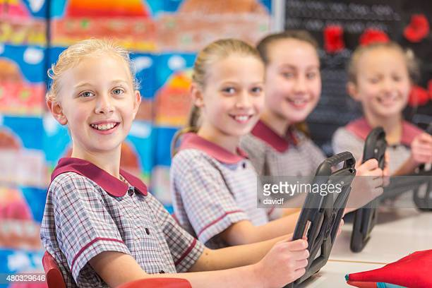 Happy School Girls Using Tablet Computers In The Classroom