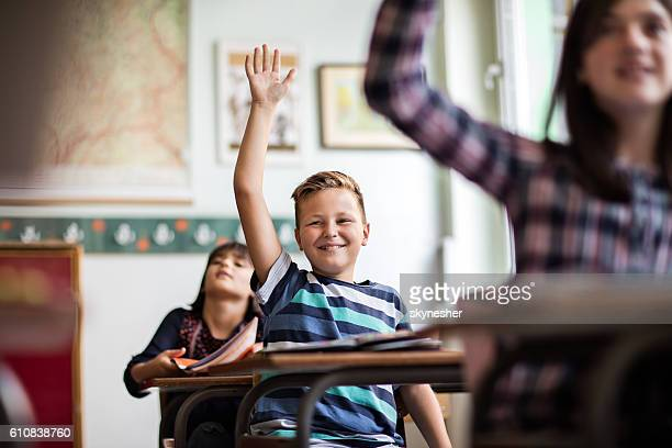 Happy schoolboy in classroom raising hand to answer the question.