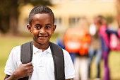 Happy schoolboy in front of the school