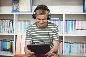 Happy schoolboy listening music while using digital tablet in library at school