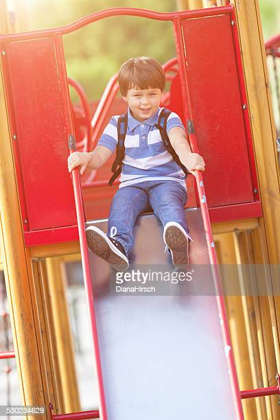 happy schoolboy on slide