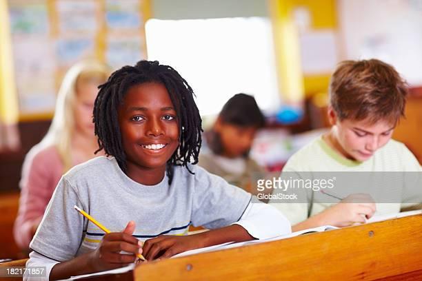 Happy schoolboy writing in classroom