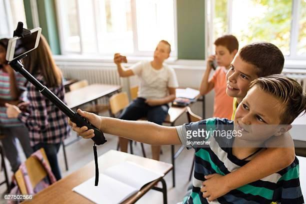 Happy schoolboys taking selfie on a break in classroom.
