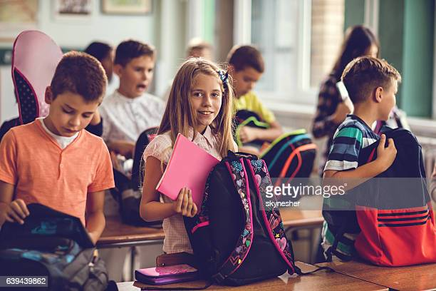 Happy schoolgirl and her classmates packing school supplies after class.