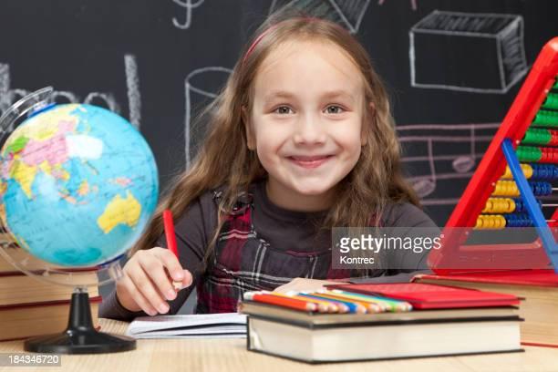Happy schoolgirl doing homework