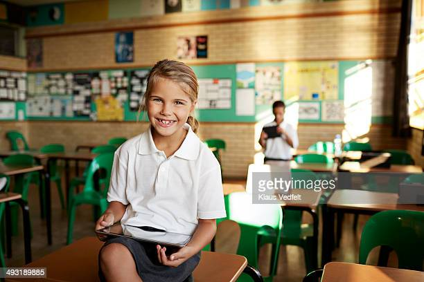 Happy schoolgirl holding tablet