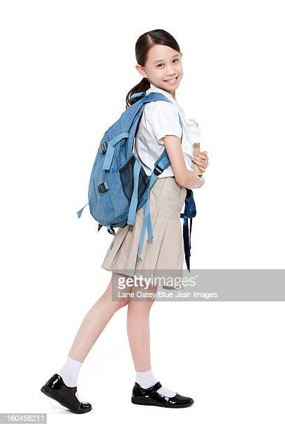 Happy schoolgirl with books and schoolbag on the back