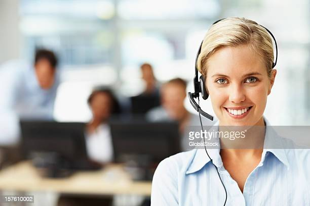 Happy secretary wearing a headset with colleagues at the back