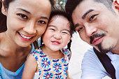 A happy selfie family potriat of three