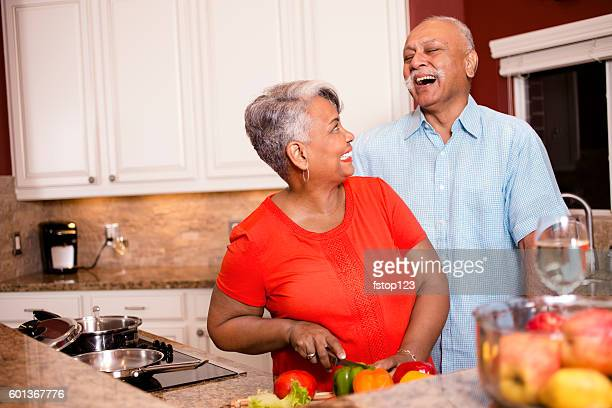 Happy senior adult couple cooking together in home kitchen.