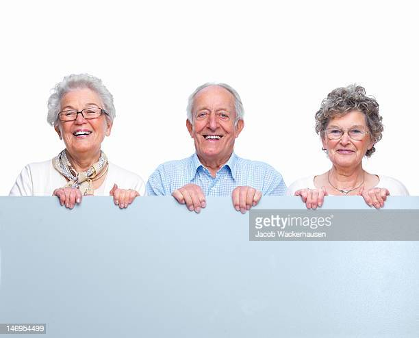 Happy senior adults holding placard