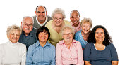 A multi-ethnic group of senior adults are standing together in a group - they are smiling and looking at the camera.