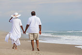Happy romantic senior African American man and woman couple walking holding hands on a deserted tropical beach